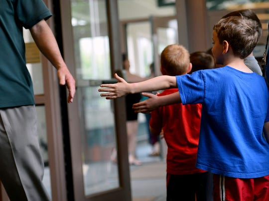 Elementary school students stick their hands out waiting for high-fives from Williamston High School seniors on  Friday.