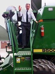 "Recruiting Iowans to his ""farm team"" to help win the Iowa caucuses, Republican presidential candidate George W. Bush climbs aboard a combine on a farm near Dallas Center on Sept. 1, 1999."