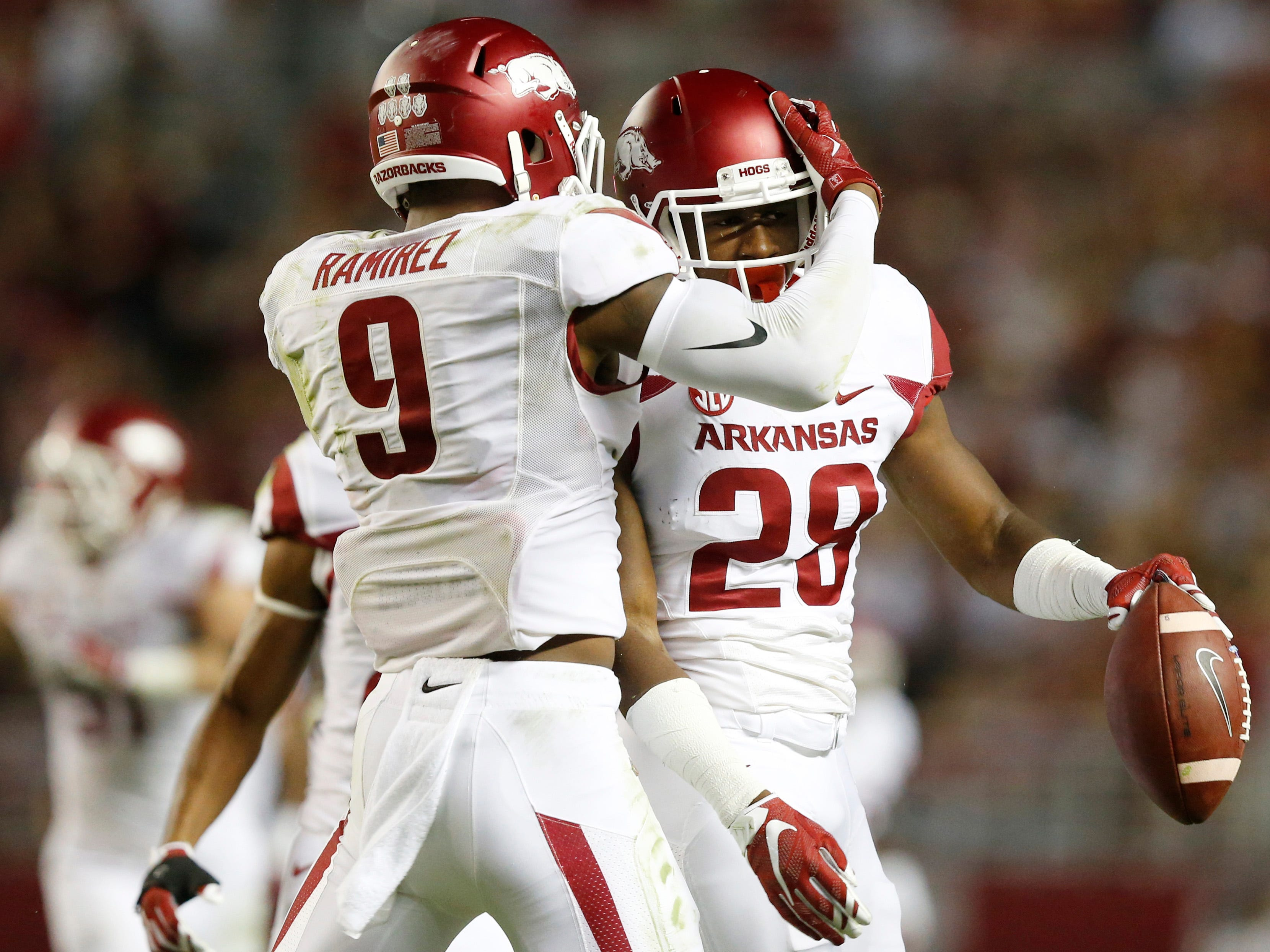 Arkansas defensive back Josh Liddell (28) celebrates with defensive back Santos Ramirez (9) after Liddell intercepts the ball intended for Alabama tight end O.J. Howard (88) in the first half of an NCAA college football game, Saturday, Oct. 10, 2015, in Tuscaloosa, Ala. (AP Photo/Brynn Anderson)