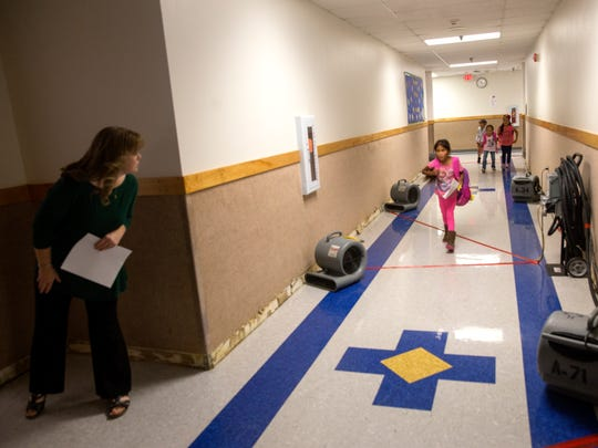 Teacher and students use a hallway, Thursday, Sept. 15, 2017 in the area where  the water damage originated at Kirtland Elementary School.