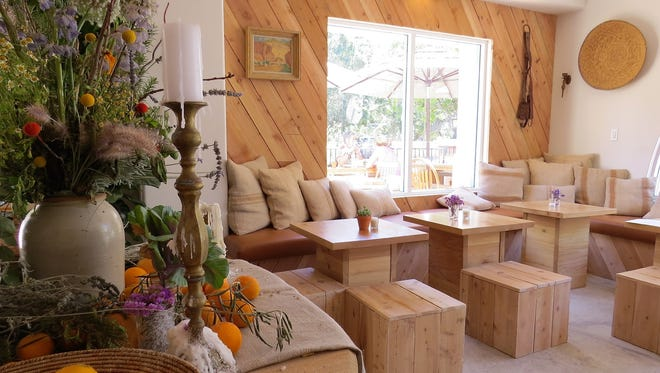 Ojai Harvest opened May 17 at what used to be Los Caporales Restaurant & Tequila Bar. Seating includes wood blocks in the lounge area, pictured, and traditional tables and banquettes in the dining area beyond a display table laden with candles, bundles of herbs and bowls of local citrus.