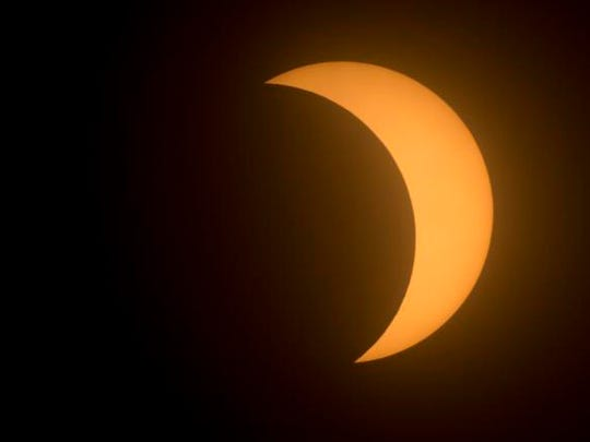 The moon covers a part of the sun during a partial