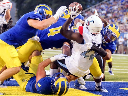 The Delaware defense, including (from left) Charles Bell, Troy and Colby Reeder and Cam Kitchen tackles Delaware State running back Mike Waters for a safety in the first quarter at Delaware Stadium in August, 2017.