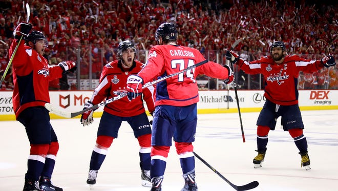 John Carlson of the Washington Capitals is congratulated by his teammates after scoring a second-period goal.