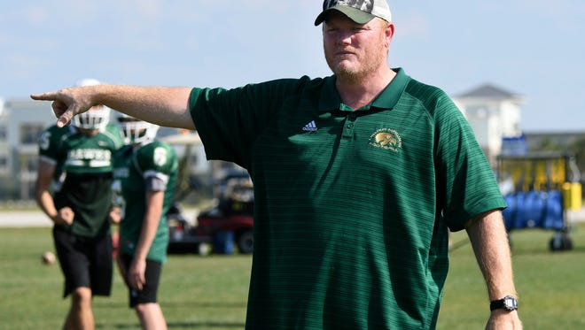 Viera High football coach Derek Smith directs his players during spring football practice at the school.