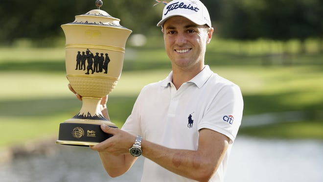 Justin Thomas holds the trophy after winning the World Golf Championship-FedEx St. Jude Invitational Sunday in Memphis.