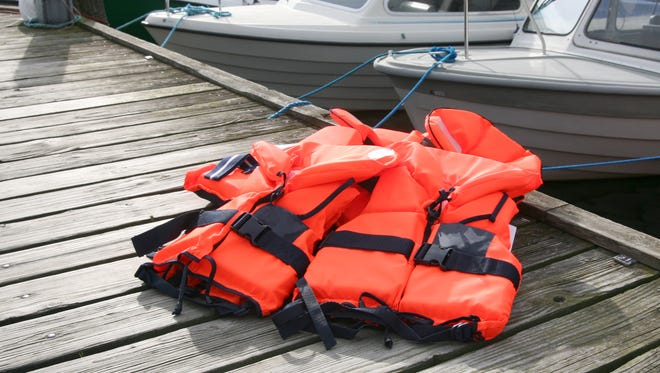 Red Life Jackets on pier with boats in background