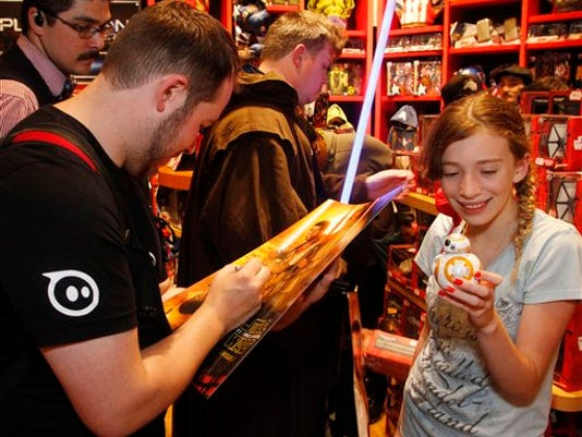 Adam Wilson, creator of the Star Wars BB-8, the new app-enabled Droid toy inspired by Star Wars: The Force Awakens, signs a poster for a smiling fan on Force Friday at Disney Store Stockton Street in San Francisco today.