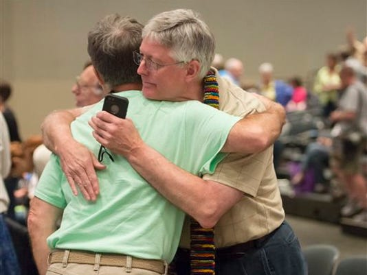 """In this June 19, 2014, file photo, Gary Lyon, left, of Leechburg, Pa., and Bill Samford, of Hawley, Pa., celebrate after a vote allowing Presbyterian pastors discretion in marrying same-sex couples at the 221st General Assembly of the Presbyterian Church at Cobo Hall, in Detroit. The Presbyterian Church (U.S.A.) approved redefining marriage in the church constitution Tuesday, March 17, 2015, to include a """"commitment between two people,"""" becoming the largest Protestant group to formally recognize gay marriage as Christian and allow same-sex weddings in every congregation."""