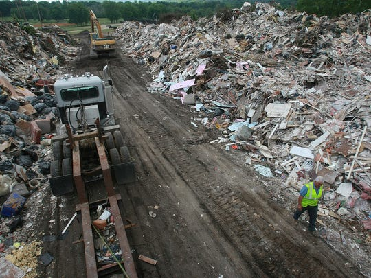 Worker Van Baker walks through tons of trash at Edwin