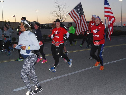 Runners 499 Kelli McFadden, of Cleves, and 422 David Lafleche, of Liberty Township, run for RWB, a veterans support group, during the second annual Honor Run half marathon held Sunday, Nov. 15, in Florence.