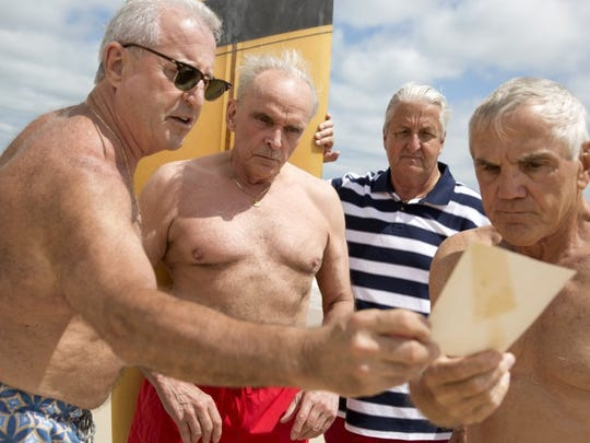 Marines buddies Dennis Puleo, from left, Tom Hanks, Bob Falk, and Bob DeVenezia view the photograph that was taken nearly 50 years prior during weapons training in Oceanside, California to memorize and recreate the scene on Cinnamon Beach Saturday, April 23, 2016 in Palm Coast, Florida. The four haven't all been in the same place since they were shipped off to fight in Vietnam.