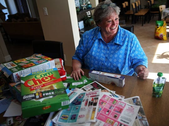 Daphne Tull organizes coupons in her home on Thursday, May 5, 2016 in Naples. Tull lost her hearing in 2011 and found new purpose in couponing for food to donate to St. Matthew's House food pantry.
