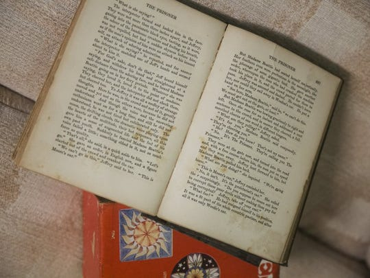 """The book """"The Prisoner"""", which was left open on a couch by the vandals, sits untouched in the Boomer House."""