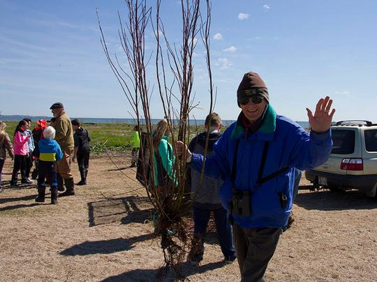 Dr. Charles Sontag helps students plant trees at the Manitowoc Containment.