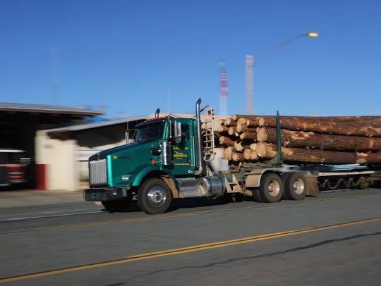 A logging truck heads along Main Street in downtown