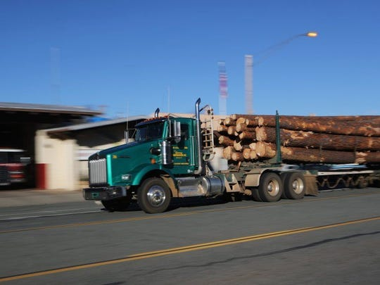 A logging truck heads along Main Street in downtown Burney in November 2016.