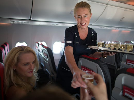 Cabin crew member Anna Ronnow serves champagne to passengers