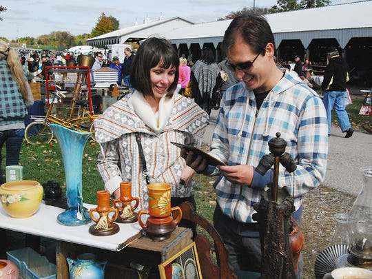 Laura Gerhold of Bellevue and Josh Rectenwald of Covington examine an antique porcelain plate during the Burlington Antiques Show held Sunday, Oct., 19, at the Boone County Fairgrounds.