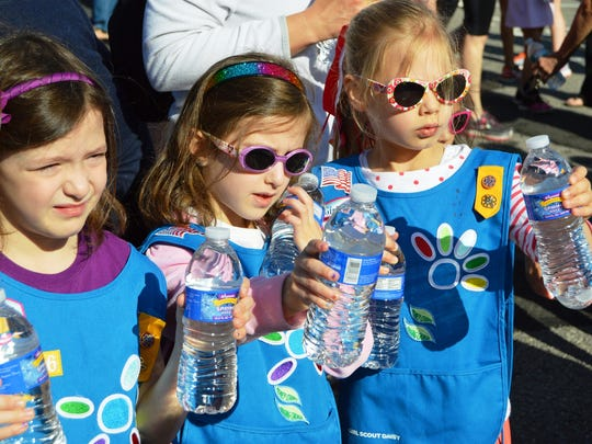 Sophie Weinglass, Carly Weinglass and Isabella Auzinger, members of the Hillsborough Daisy Troop, hand water to runners as they finish Saturday's Hillsborough Hop 5K.