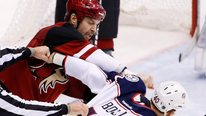 The Arizona Coyotes' John Scott (Michigan Tech) punches the Columbus Blue Jackets' Jared Boll, right, formerly of the Plymouth Whalers, on Dec. 17, 2015, in Glendale, Ariz.