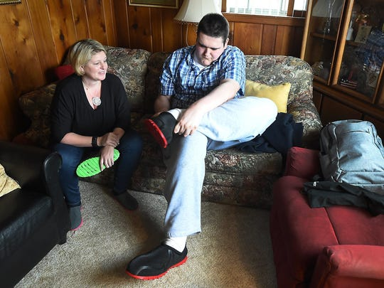 Broc Brown puts on his new shoes as Feetz CEO Lucy