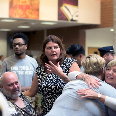 Friends and family of Amy Girard embrace after Thursday's