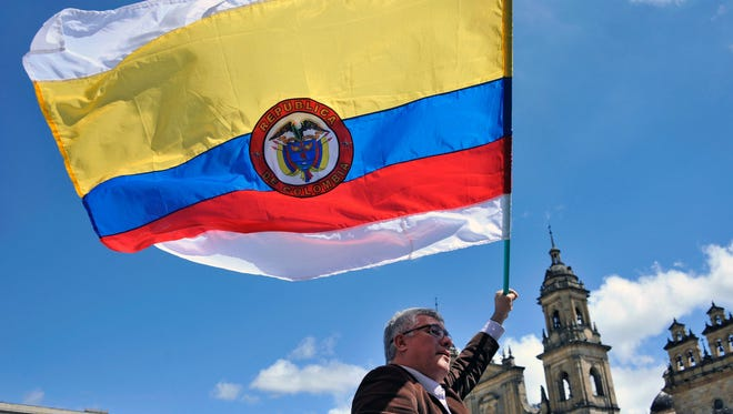 A man holds a Colombian national flag with white stripes during a demo to demand the immediate endorsement of the new peace agreement between the Colombian government and the FARC guerrilla outside the Colombian Congress in Bogota.