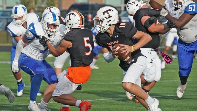 Taunton High quarterback Trent Santos (10) looks to avoid the rush of Attleboro defenders during last year's game at Taunton High School. The football season will not have Thanksgiving Day games this fall and will get pushed back until late February.