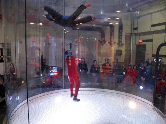 """Children and adults are kept airborne by updrafts inside of a wind tunnel; they """"fly"""" under the watchful eye of an experienced skydiver at iFLY."""