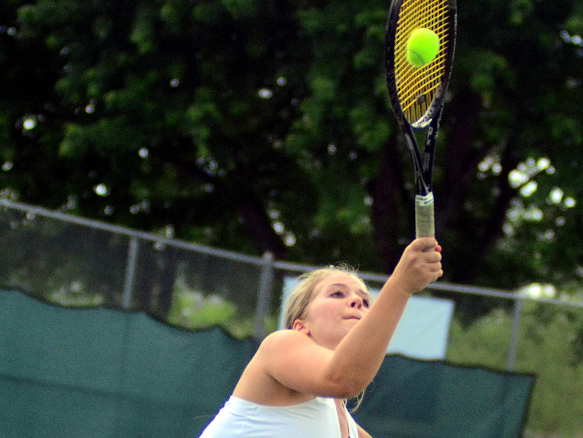 Hendersonville High junior Grace Phillips hits an overhead volley during Wednesday's doubles semifinals.