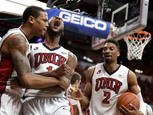 UNLV's Roscoe Smith, center, reacts after a foul with his teammates Bryce Dejean-Jones, left, and Khem Birch during the first half of an NCAA college basketball game against Wyoming in the quarterfinals of the Mountain West Conference men's tournament Thursday, March 13, 2014, in Las Vegas. (AP Photo/Isaac Brekken)