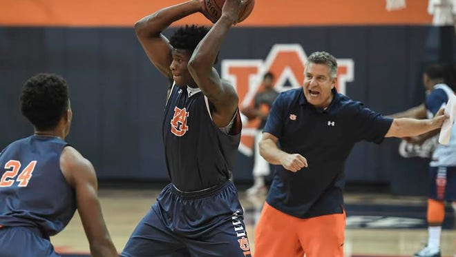 Auburn head coach Bruce Pearl shouting instructions while Danjel Purifoy has the ball being guarded by Anfernee McLemore (24).
