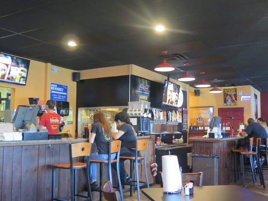 Border Burger Bar's dining area features a counter, where patrons can enjoy food and drinks, and watch sports on several TVs. The restaurant is located at 3329 Fort.
