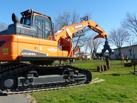 People watch the driver of a Doosan excavator attempt