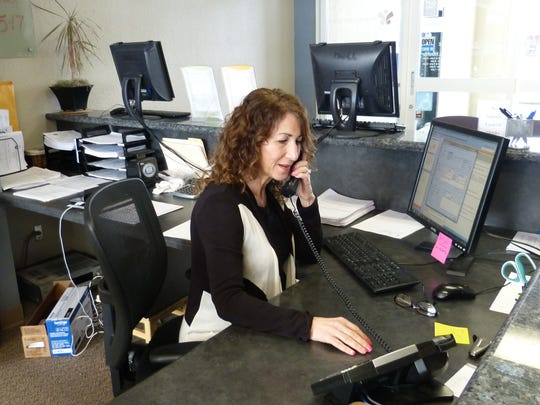 Giselle Harris, receptionist at Wellness of Redding calls to inform patients their office is open.
