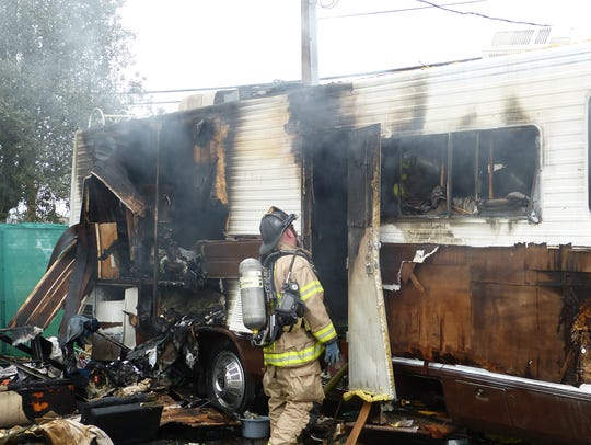 A firefighter inspects an RV that was destroyed in