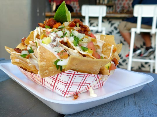 The nachos ($5) from Fools Gold are stacked with homemade corn chips, pico de gallo and al pastor-marinated pork.