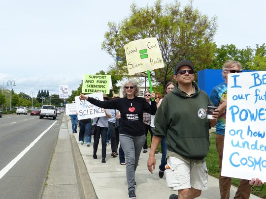 Cars honk their horns in support of people passing by during Redding's March for Science on Saturday.