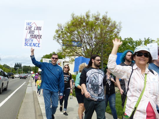 """Mike Basial, 46, left, inspired by """"Star Trek,"""" holds up a sign as he took part in the March for Science."""