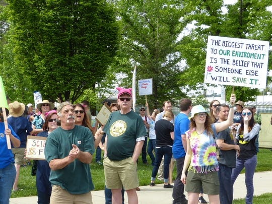 People stand on Cypress Avenue waving signs for the