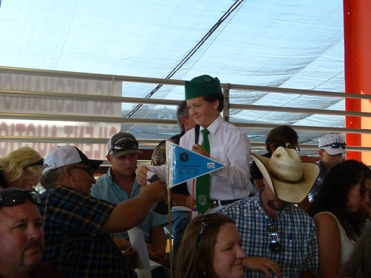 Wyatt Coburn, 12, shakes hands and gives a hat to the