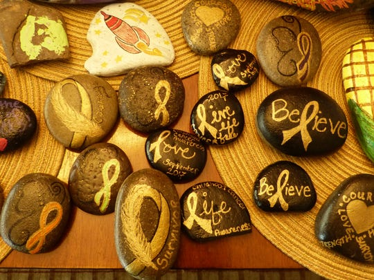 Hudgen said the rocks, which have positive messages inscribed on them, help lift people up.