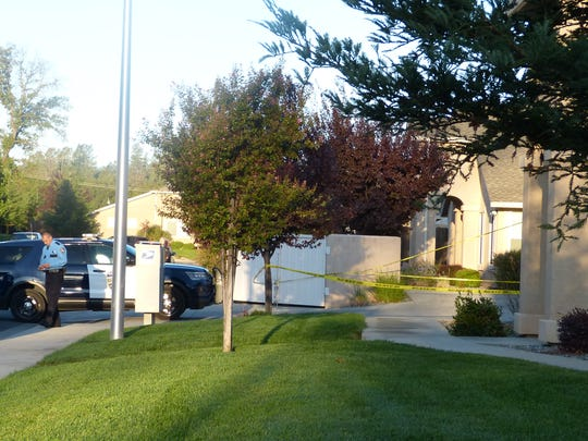 Crime tape surrounds the town home complex where a homicide is investigated on Thursday.