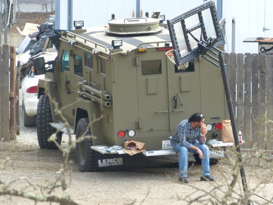 An unidentified man sits on the back of a SWAT team