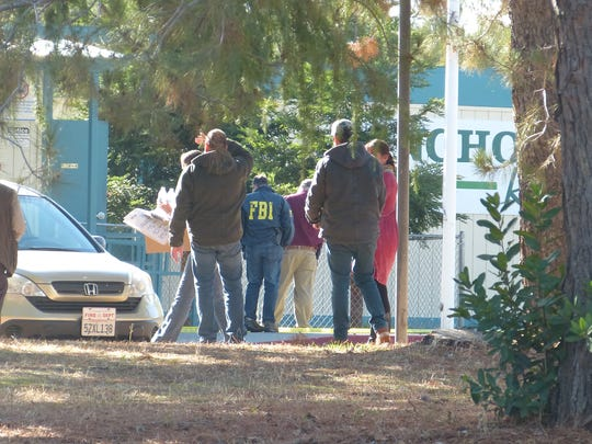 Law enforcement officials, including an FBI agent, and others gather Tuesday outside the Rancho Tehama Elementary School.