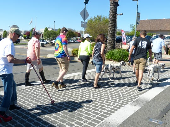 People walk along Hilltop Drive on Saturday morning for One SAFE Place's Walk a Mile in Her Shoes event.