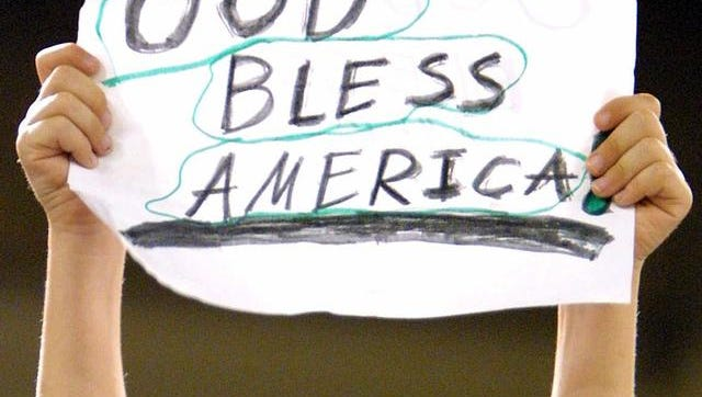 "Hands hold handwritten ""God Bless America"" sign"