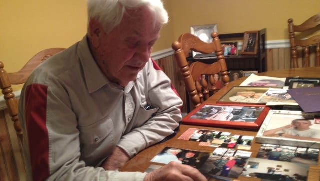 George Wayne Griffin Sr., 73, the father of one of the men killed last week in a helicopter crash off the Florida coast, looks over old photographs of his son, Chief Warrant Officer 4 George Wayne Griffin Jr.