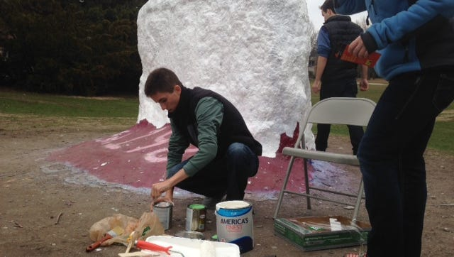Connor Sexton prepares to paint the rock in honor of Lacey